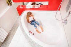 Mädchen, das im Badezimmer, spielend in der Tablette sich versteckt lizenzfreie stockfotos
