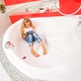 Mädchen, das im Badezimmer, spielend in der Tablette sich versteckt stockfoto