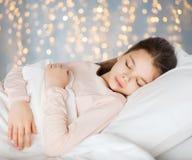 Mädchen, das im Bett über Feiertagslichtern schläft stockbild
