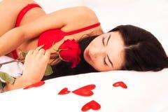 Mädchen, das im Bett, gestreut mit Inneren und Rosen liegt Stockbilder