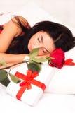 Mädchen, das im Bett, gestreut mit Inneren und Rosen liegt Lizenzfreie Stockfotografie