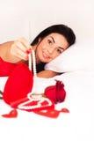 Mädchen, das im Bett, gestreut mit Inneren und Rosen liegt Lizenzfreies Stockbild