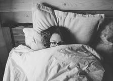Mädchen, das im Bett liegt und Sie betrachtet Stockbild