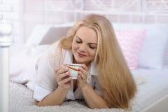 Mädchen, das im Bett mit einem Tasse Kaffee liegt Stockfoto