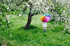 Mädchen, das im blühenden Garten mit buntem Regenbogenregenschirm steht Frühling, draußen stockbild