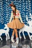 Mädchen, das im Blau und in den Dekorationen der weißen Weihnacht steht Lizenzfreies Stockbild