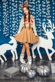 Mädchen, das im Blau und in den Dekorationen der weißen Weihnacht steht Stockfotos