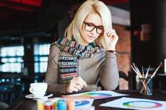 Mädchen, das im Café mit Tasse Kaffee und dem Zeichnen sitzt Stockfotografie