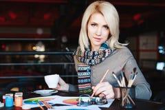 Mädchen, das im Café mit Tasse Kaffee und dem Zeichnen sitzt Lizenzfreie Stockbilder