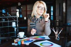 Mädchen, das im Café mit Tasse Kaffee und dem Zeichnen sitzt Stockbilder