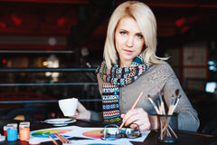 Mädchen, das im Café mit Tasse Kaffee und dem Zeichnen sitzt Stockfoto
