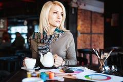 Mädchen, das im Café mit Tasse Tee und Zeichnungen sitzt Lizenzfreie Stockfotografie