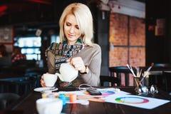 Mädchen, das im Café mit Tasse Tee und Zeichnungen sitzt Stockfoto