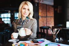 Mädchen, das im Café mit Tasse Tee und Zeichnungen sitzt Stockbild
