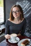 Mädchen, das im Café sitzt Lizenzfreie Stockfotografie