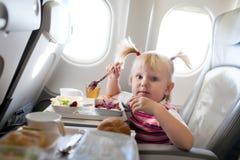 Mädchen, das im Flugzeug isst Stockfoto
