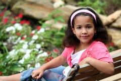 Mädchen, das im Garten sitzt Stockfotos