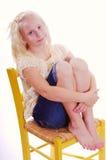 Mädchen, das im gelben Stuhl umarmt ihre Fahrwerkbeine sitzt Lizenzfreies Stockbild