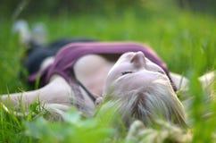 Mädchen, das im Gras sich entspannt Stockbild