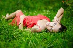 Mädchen, das im hellen Gras des grünen Sommers liegt Stockfotografie