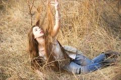 Mädchen, das im hohen Gras aufwirft Lizenzfreie Stockfotos