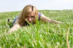 Mädchen, das im hohen Gras sich entspannt. Stockfoto
