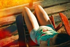 Mädchen, das im Lehnsessel auf einem Rest mit einem hellen Leck sitzt Stockfotografie