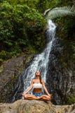 Mädchen, das im Naturwasserfall sitzt und meditiert stockfoto