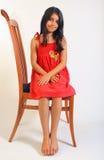 Mädchen, das im roten Kleid sitzt Lizenzfreies Stockbild