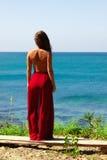 Mädchen, das im roten Rock über dem Seeschauen schulterfrei steht lizenzfreies stockbild