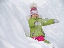 Mädchen, das im Schnee spielt Stockbild