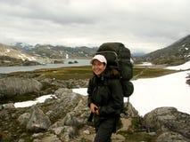 Mädchen, das im Schneefeld und im rockfield wandert Lizenzfreie Stockfotografie