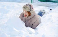Mädchen, das im Schneehaufen liegt Lizenzfreie Stockfotos