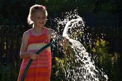Mädchen, das im Sonnenlicht Wasser spritzt Stockfoto