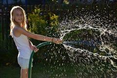 Mädchen, das im Sonnenlicht Wasser spritzt Lizenzfreies Stockfoto