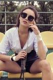 Mädchen, das im Stadion mit einem Schläger für Tennis sitzt Stockbild