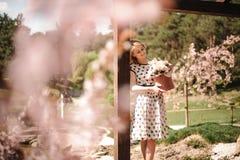 Mädchen, das im summerhouse mit einem Kasten Blumen steht Stockbild
