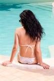 Mädchen, das im Swimmingpool ein Sonnenbad nimmt Stockfotografie