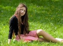 Mädchen, das im Thpark sitzt lizenzfreie stockfotografie