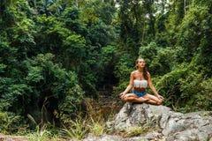 Mädchen, das im Wald auf Felsen sitzt und meditiert stockfoto