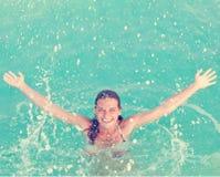 Mädchen, das im Wasser spritzt Stockbild