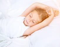 Mädchen, das im weißen Bett schläft Stockfotos