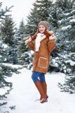 Mädchen, das im Winterpark am Tag aufwirft E Rothaarigefrau in voller Länge Stockfoto