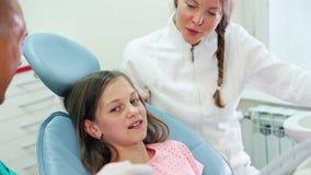 Mädchen, das im zahnmedizinischen Stuhl gibt Zahnarzt und dem Assistenten Hoch fünf sitzt stock video footage