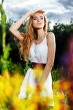 Mädchen, das innen auf einer Blumenlichtung und -blicken steht stockbild