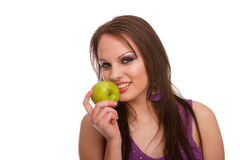 Mädchen, das innen zu einem grünen Apfel beißt Lizenzfreie Stockfotos