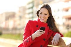 Mädchen, das am intelligenten Telefon sitzt in einem Park simst Stockbild
