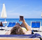 Mädchen, das intelligentes Mobiltelefon auf einem Strand mit Meer auf dem Hintergrund betrachtet für Entspannungs- und Kommunikat Stockbilder