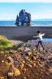 Mädchen, das Jugendlicher über Wasserstrom in der Grenze von Hindisvik-Bucht in Nordwest-Island, der Hvitserkur-Basaltstapel spri stockbild