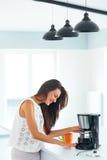 Mädchen, das Kaffee zum Frühstück in der Küche macht lizenzfreies stockbild